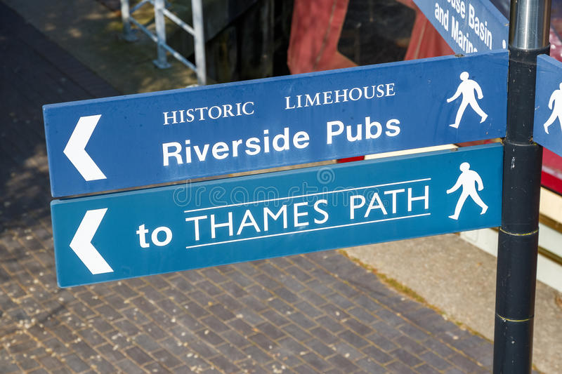Riverside Pubs and Thames Path street sign. In London with a narrowboat in the background royalty free stock image