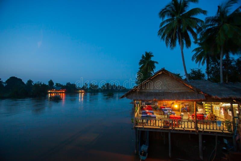 Riverside restaurant near Mekong River at twilight. Coconut trees silhouette, Beautiful lighting, restaurant and sunset sky stock photos