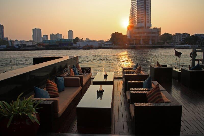 Riverside restaurant seats during sunset royalty free stock photos