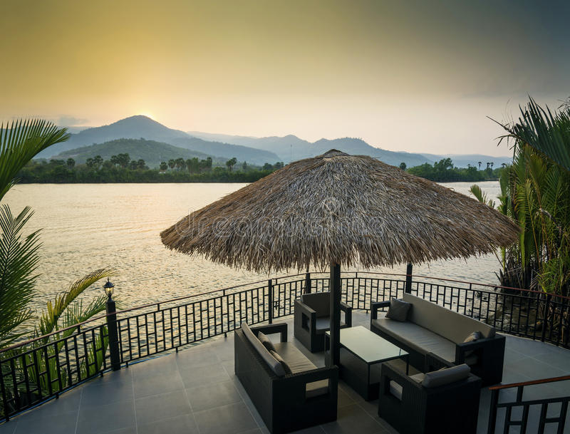 Riverside sunset view in kampot cambodia asia with deck sofas. Riverside sunset view in kampot cambodia asia with relaxing deck sofa chairs and table stock photography