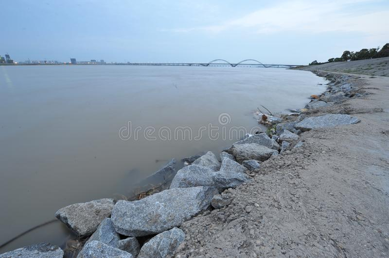 Riverside -urban fringe. The edge of a city, in the distance is the modern tall building and the cross river bridge and the skyline stock image