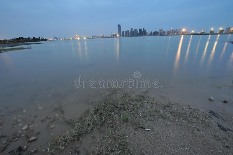 Riverside -urban fringe. The edge of a city, in the distance is the modern tall building and the cross river bridge and the skyline royalty free stock photos