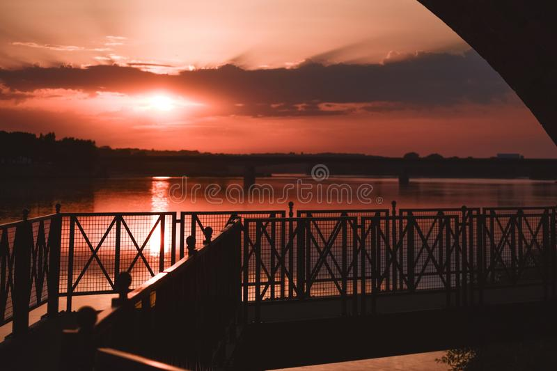 Riverside walk in a colorful sunset backlight royalty free stock images