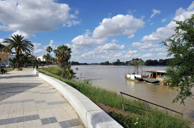 Riverside walk in the river Guadalquivir as it passes through Coria del Rio, Seville province, Andalusia, Spain. Fishing boats and barges on the River royalty free stock images
