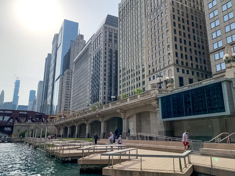RIverwalk patronage, including commuters, joggers, and businessman fishing, along Chicago River stock photos