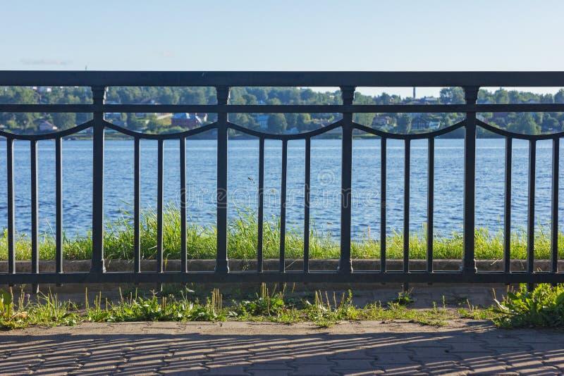 Rivesta di ferro il recinto davanti al fiume un giorno soleggiato immagini stock
