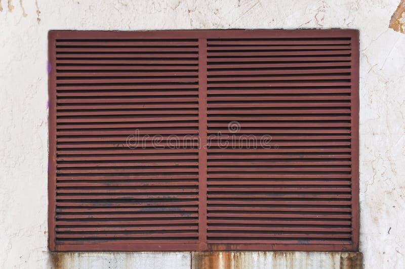 Rivesta di ferro la finestra chiusa marrone sulla facciata bianca di struttura con la parete ruvida fotografia stock