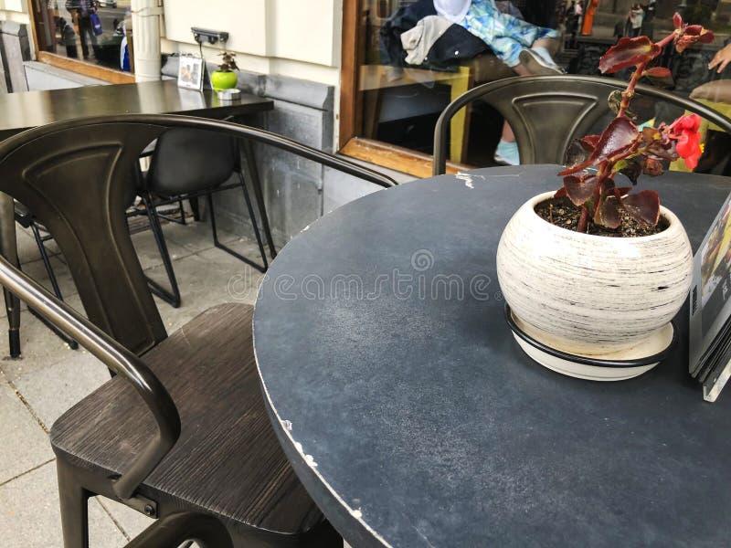 Rivesta di ferro la tavola in un caffè sulla via principale Fiori sulla tabella fotografia stock