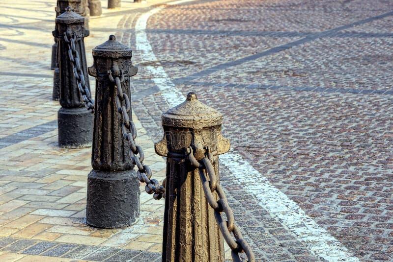 Rivesta di ferro le vecchie colonne con la catena sul marciapiede vicino alla strada immagine stock libera da diritti