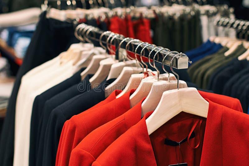 Rivestimenti della donna in colori rossi, blu, bianchi ed altri sui ganci in un deposito dettagliante dei vestiti immagini stock libere da diritti