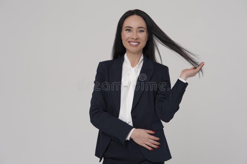 Rivestimento d'uso e blusa della giovane persona di affari castana affascinante della donna fotografia stock