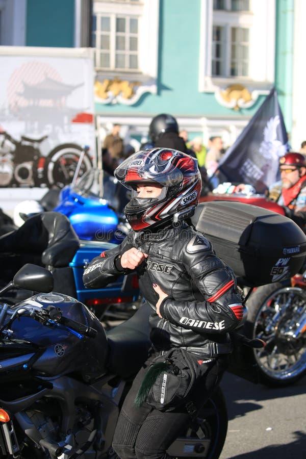 Rivestimento dei bottoni del motobiker della donna davanti allo specchio del suo motociclo immagine stock libera da diritti