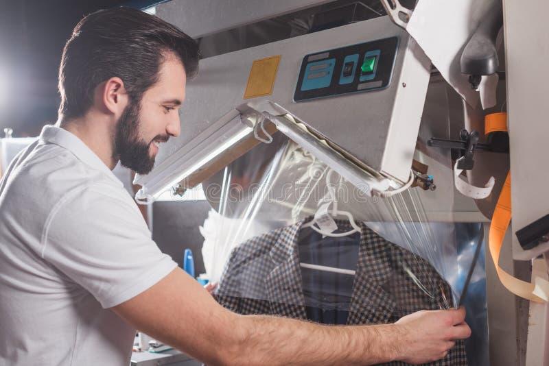 rivestimento dell'imballaggio del lavoratore di lavaggio a secco fotografia stock