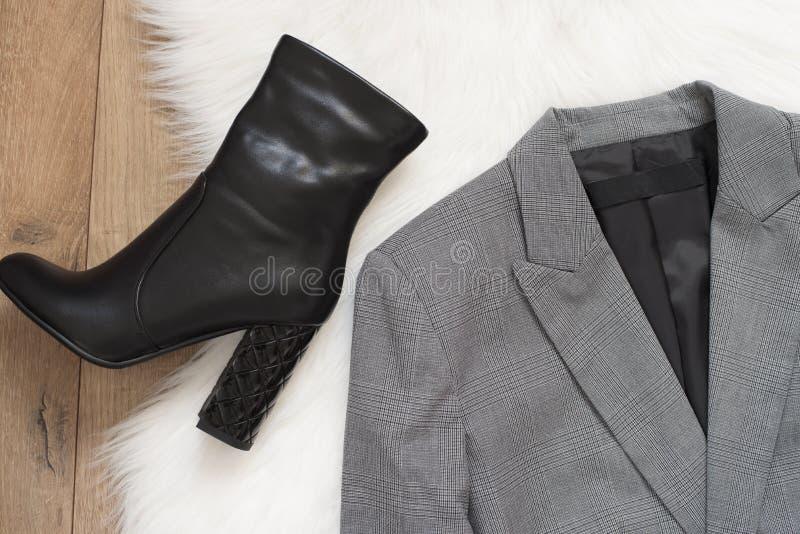 Rivestimento delle donne eleganti e stivali neri del tacco alto A quadretti un rivestimento grigio su un fondo di legno Concetto  immagine stock libera da diritti
