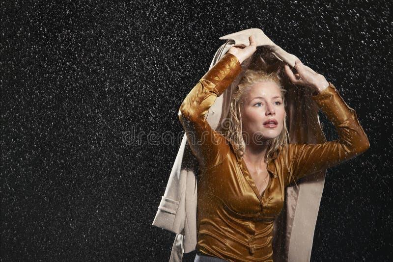Rivestimento di Covering Head With della donna di affari in pioggia immagine stock