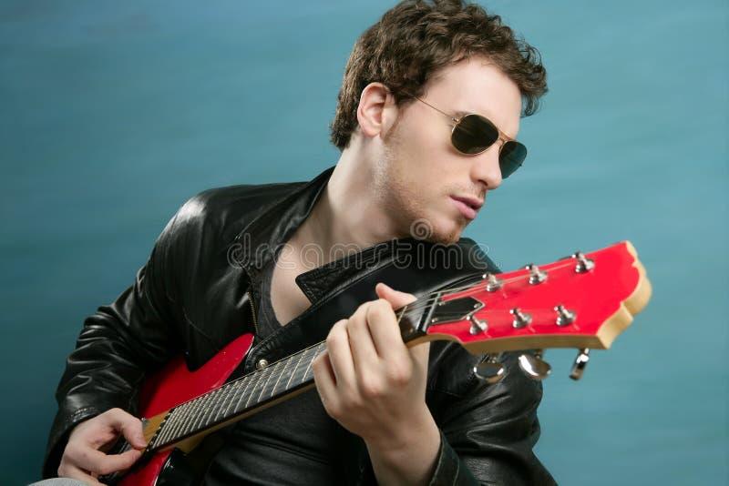 Rivestimento di cuoio degli occhiali da sole dell'uomo del rock star della chitarra fotografia stock libera da diritti