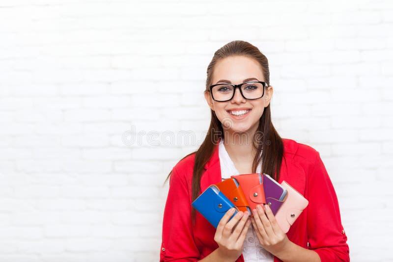 Rivestimento felice di rosso di usura di sorriso dei portafogli dei biglietti da visita della tenuta della donna di affari immagini stock libere da diritti
