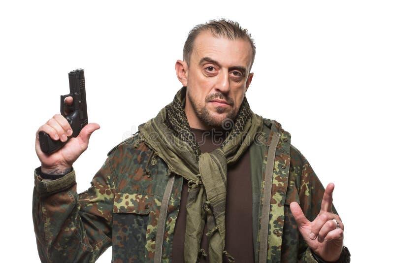 Rivestimento maschio dei militari del terrorista pistola in sua mano fotografie stock