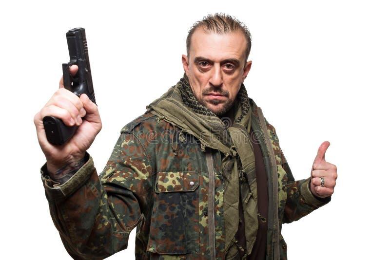 Rivestimento maschio dei militari del terrorista pistola in sua mano immagini stock libere da diritti