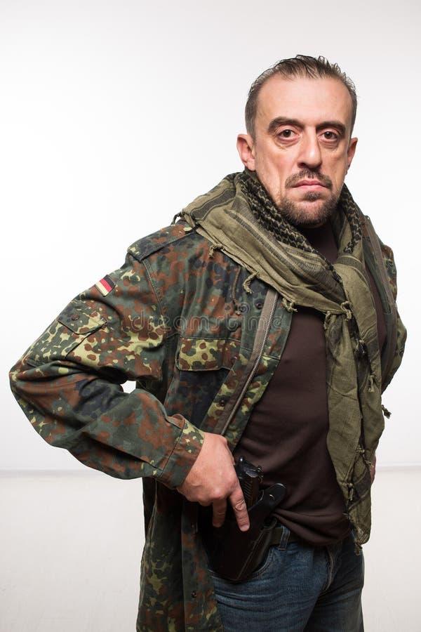 Rivestimento maschio dei militari del terrorista pistola in sua mano immagine stock libera da diritti