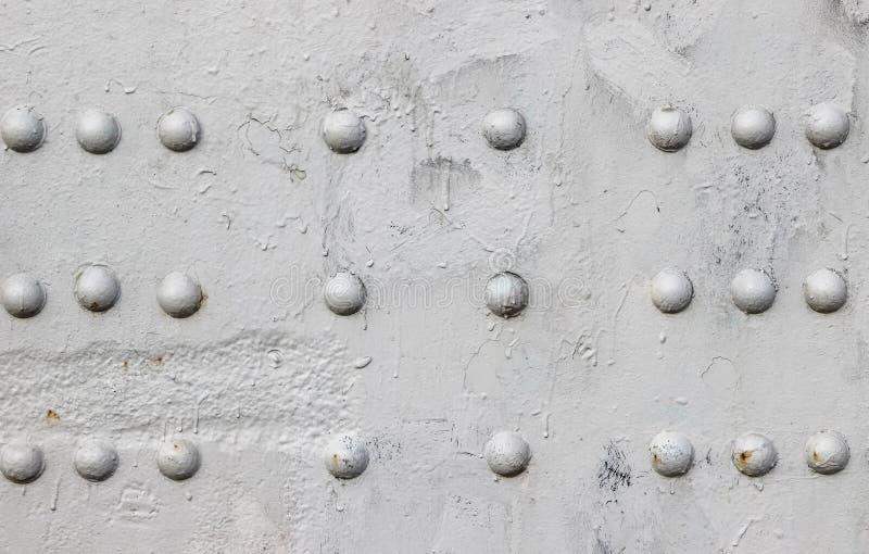 Riveté avec le détail de plaque métallique de rivets tête de bouton d'un pont peint dans le gris image libre de droits