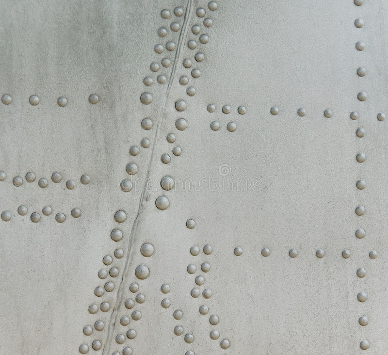 Riveted metal from aircraft. Metallic background with rivets, part of the old airplane shell stock photos