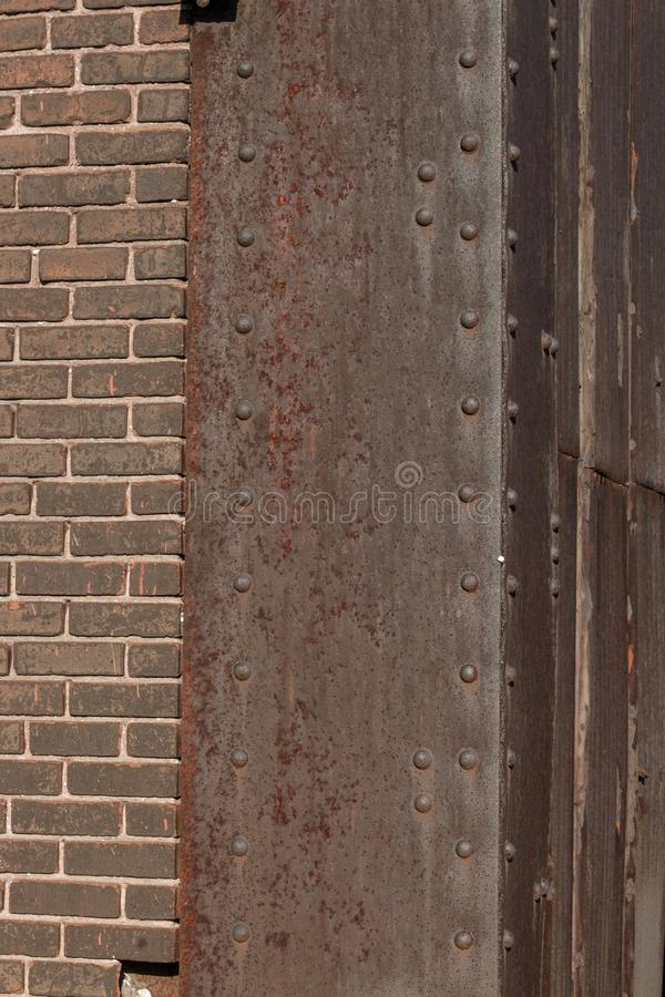 Riveted steel corner with heavy rust patina, brown brick, copy space stock image