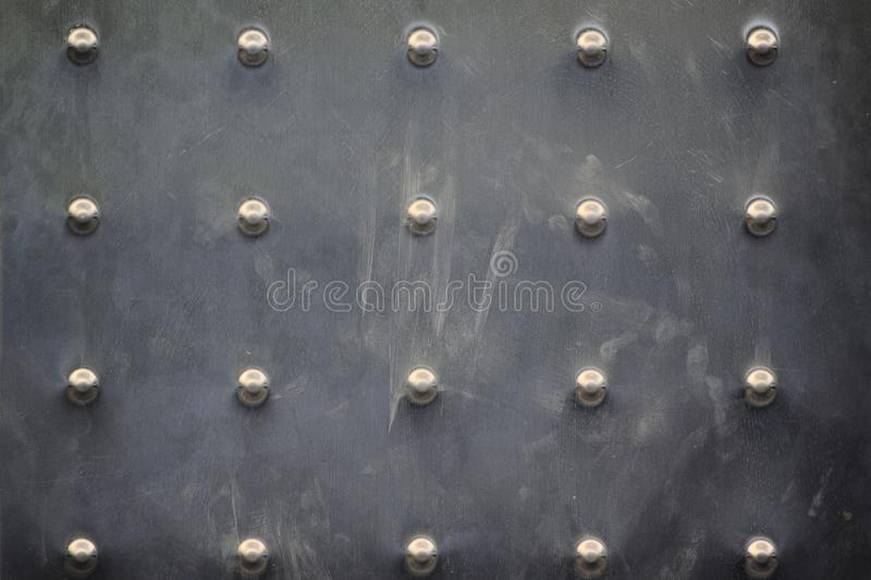 Rivets on a metal clinched veneer. Frame background and empty copy space. For Editor`s text royalty free stock photography