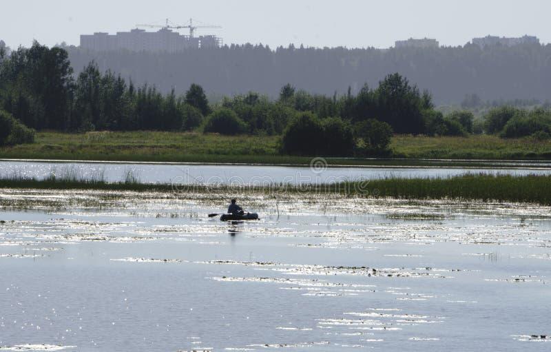 Rivière à l'aube et la silhouette d'un pêcheur dans un bateau dans la distance La réflexion du ciel dans l'eau Fond, ple image libre de droits
