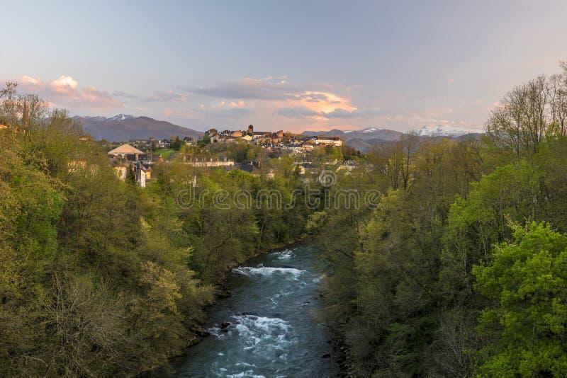 Rivière d'Oloron et ville d'Oloron-Sainte-Marie dans la lumière de coucher du soleil Les montagnes de Pyrénées atlantiques frança image libre de droits