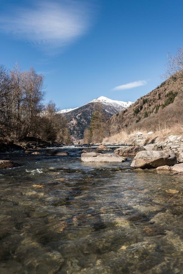 Rivière de Noce entourée par les Alpes italiens de montagnes couronnées de neige photos stock