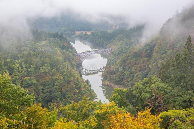 Rivière de pont et de Tadami avec le train croisant le pont photographie stock libre de droits