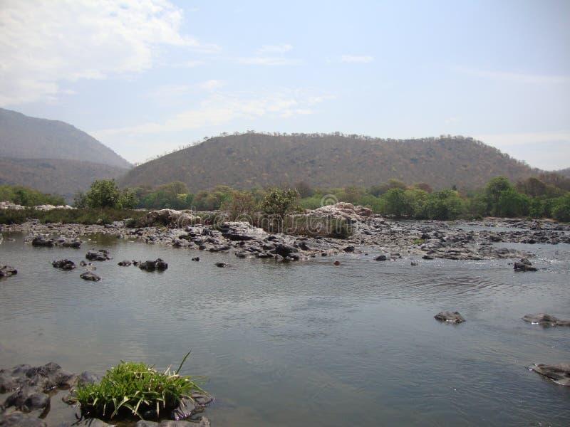 Rivière entourée de collines et moins d'eau photographie stock