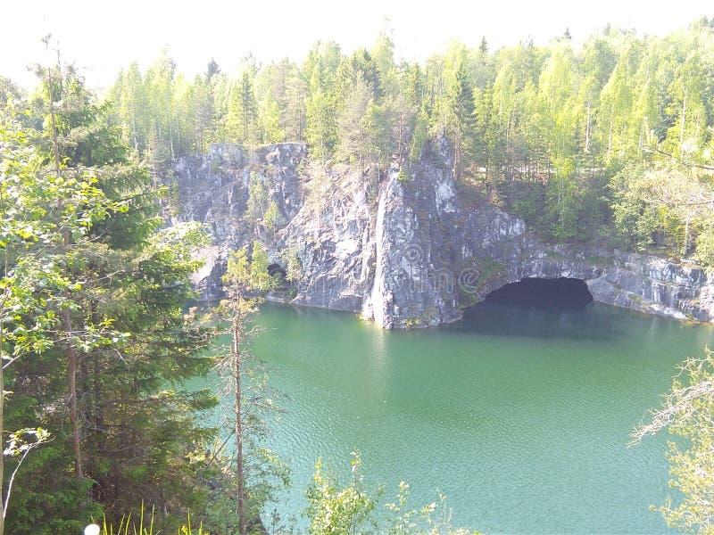 Rivière et roche avec une grotte pendant l'été photographie stock