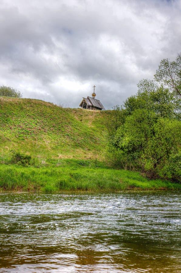 Rivière et une église en bois sur la colline image stock