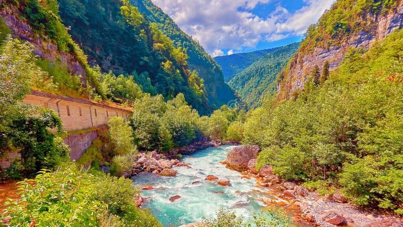 Rivière fraîche et froide de montagne dans l'heure d'été sous le ciel bleu ensoleillé nuageux photos stock
