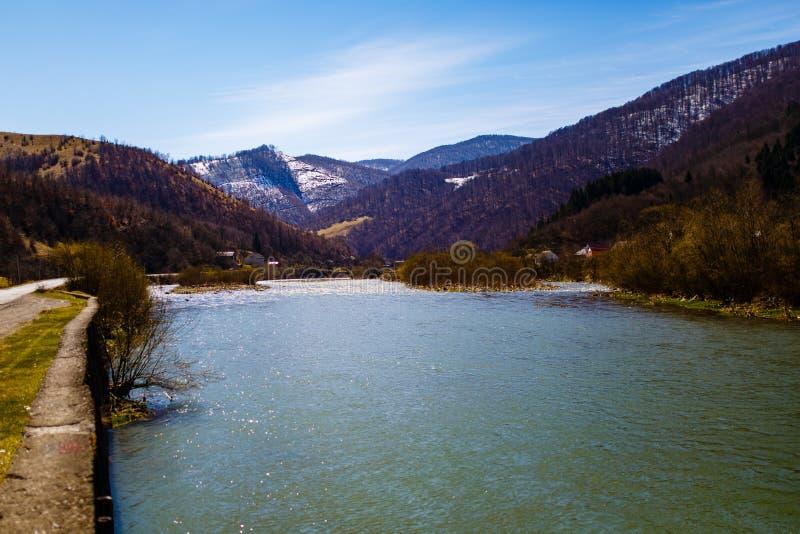 Rivière large de montagne coulant le long de la route Paysage d'avril photo stock