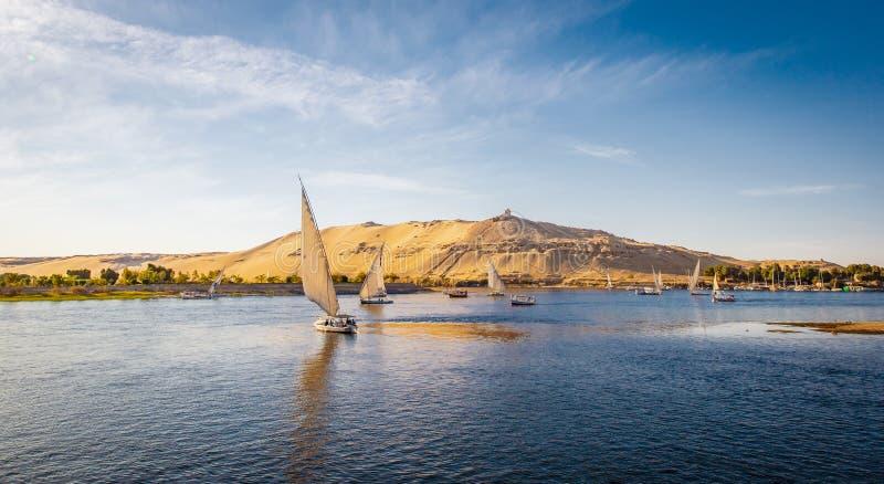 Rivière Nile Panorama d'Assouan avec des bateaux de Felucca au coucher du soleil photos stock