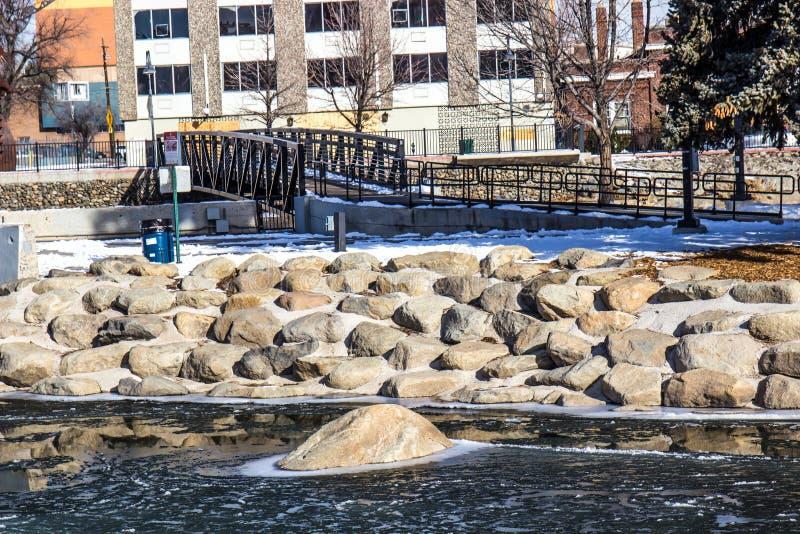 Rivière Shoreline en hiver avec les rochers, la neige et le pont de marche photos stock