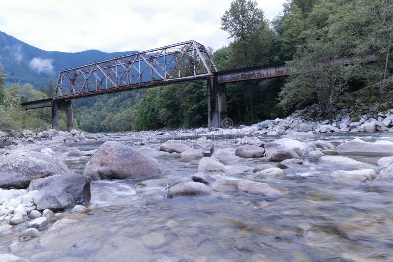 Rivière sous le vieux pont en voie ferrée photo stock