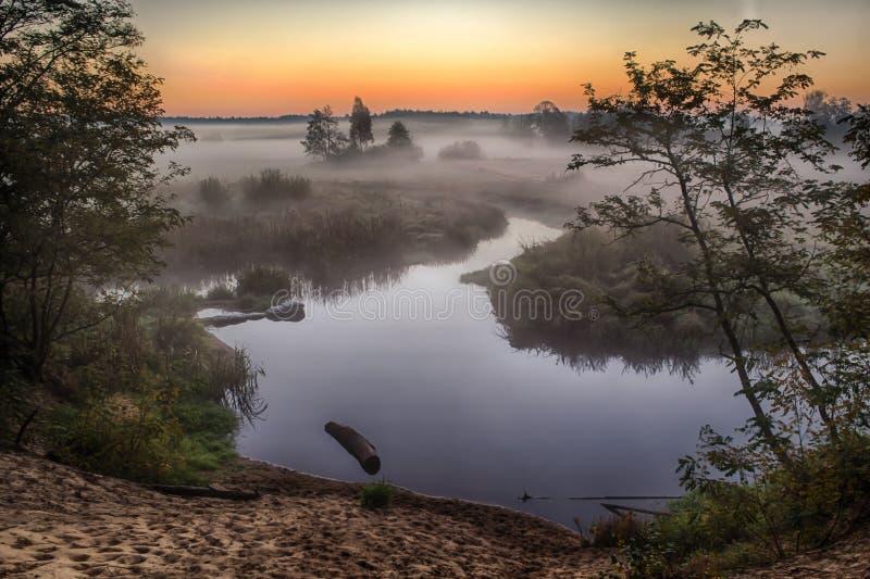 Rivier in de mist, vlak vóór zonsopgang Een warme gloed in de wolken van de eerste stralen van de zon royalty-vrije stock foto's