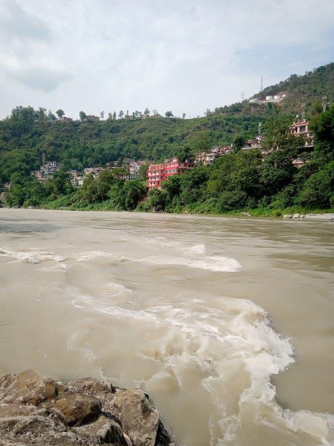 Rivier die aan een bergstad stromen stock fotografie