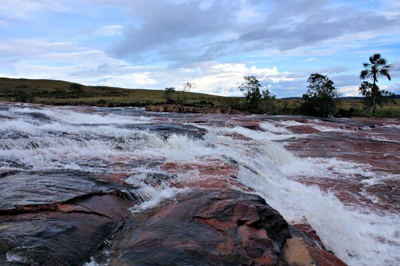 Rivier die over rode jaspis in gran sabana stromen stock foto's