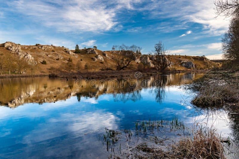 Rivier in een vallei naast rotsachtige heuvels royalty-vrije stock afbeelding