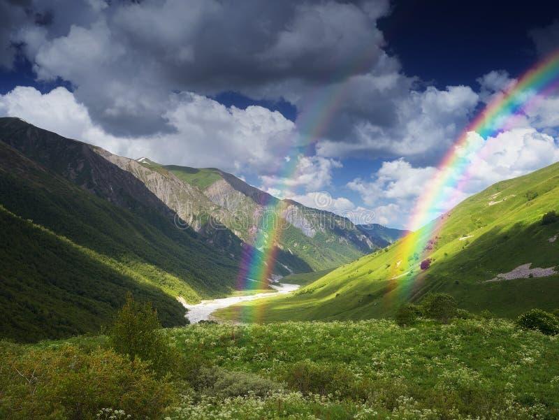 Rivier en regenboog in de bergen stock afbeelding