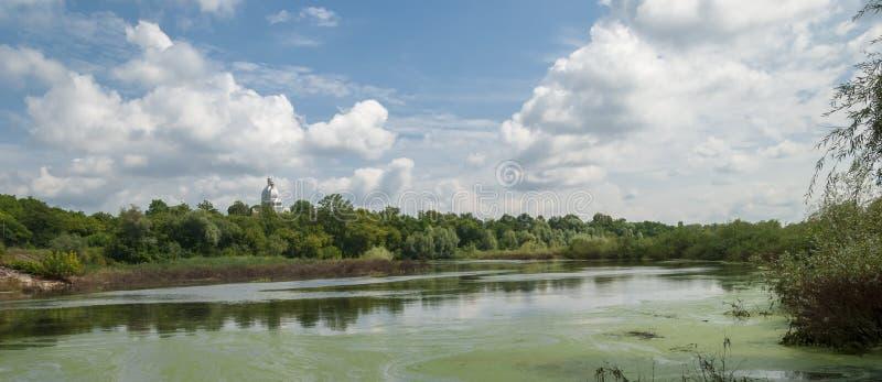 Rivier met blauwe hemel en wolken in de zomerdag stock fotografie
