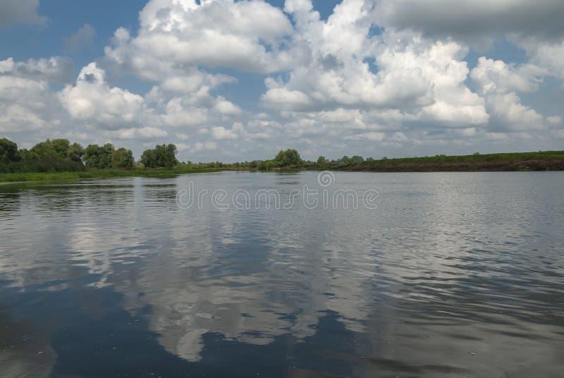 Rivier met blauwe hemel en wolken in de zomerdag royalty-vrije stock fotografie