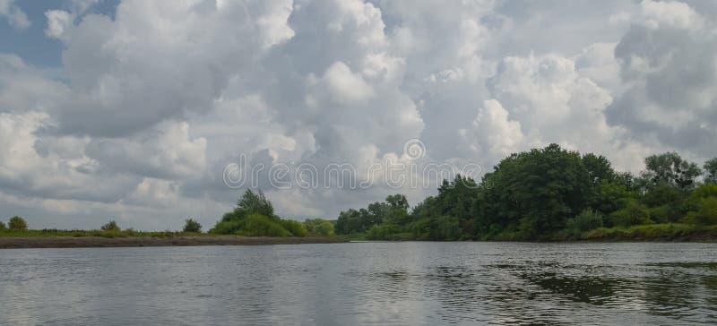 Rivier met blauwe hemel en wolken in de zomerdag royalty-vrije stock foto's