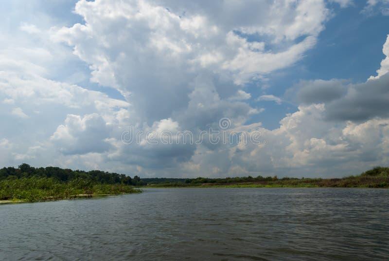 Rivier met blauwe hemel en wolken in de zomerdag royalty-vrije stock afbeeldingen