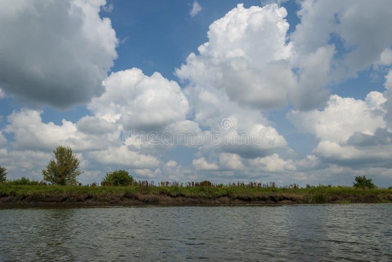 Rivier met blauwe hemel en wolken in de zomerdag stock foto's